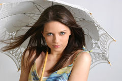 Young brunette girl with umbrella in white.  royalty free stock photography