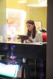 Young brunette girl using tablet in the cafe Stock Images