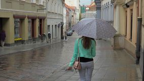 A young brunette girl is walking in rainy weather under an umbrella. The girl is walking in rainy weather under an umbrella. Goes down to the bottom of the old stock video