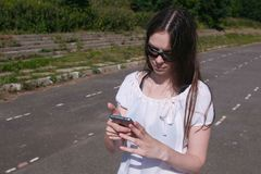 Young brunette girl walking in the stadium in a residential area and messaging on a mobile phone. stock images
