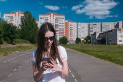 Young brunette girl walking in the stadium in a residential area and messaging on a mobile phone. royalty free stock photo