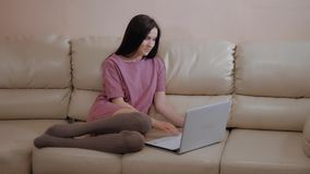 Young Brunette Girl In a Warm Socks Stockings, Lays On Leather Sofa at Home And Working On Laptop stock footage