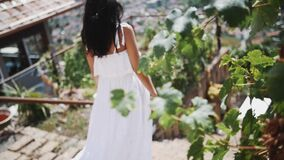 Young girl in white dress standing walking stairs of villa, city on background. Young brunette girl in white dress walking on stairs of villa, city on background stock video