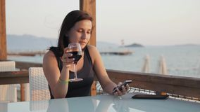Young Brunette With Glass of Red Wine Using Her Smartphone While Sitting In Cafe By The Sea at Sunset. Young Brunette With Glass of Red Wine Using Her stock footage
