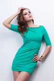 Young brunette in green dress posing in the studio Royalty Free Stock Photography