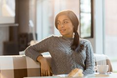 Restful woman. Young brunette in grey knitted sweater sitting on sofa in modern cozy cafe and having rest Stock Images