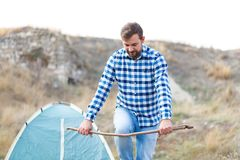A brunette guy with a beard breaks a branch. In the background is a tent. Outside. A young brunette guy with a beard breaks a branch about his knee. In the Stock Photo