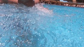 Young brunette guy jumping into the pool, shooting with action camera stock footage