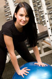 Young brunette in gym with exercise ball Royalty Free Stock Photography