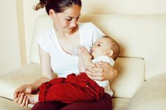 Young brunette happy mother holding toddler baby son, breast-fee. Ding concept, lifestyle modern people kissing royalty free stock photo