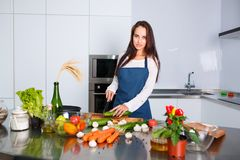 Young brunette with her hair in the kitchen cuts a cucumber Royalty Free Stock Photo