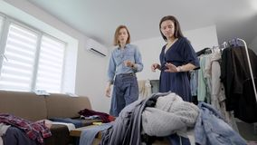 Young brunette and her stylist are checking and sorting wardrobe in home, applying clothes stock video
