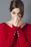 Young brunette hiding mouth and nose to sneeze for allergies Stock Images