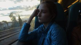 Young brunette hipster girl looking to the window in the train and thinking about her future. Day stock video
