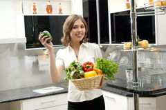 A young brunette holding vegetables in a kitchen Royalty Free Stock Images