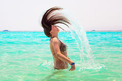Young brunette jumping out of turquoise water of Red Sea Stock Photos