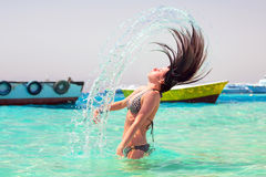 Young brunette jumping out of turquoise water of Red Sea Royalty Free Stock Photography