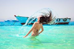 Young brunette jumping out of turquoise water of Red Sea Royalty Free Stock Photos