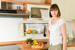 Young brunette in the kitchen Royalty Free Stock Photos