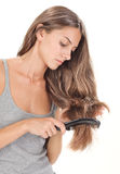 Young brunette lady combing long hairs Royalty Free Stock Images