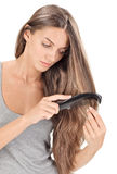 Young brunette lady combing long hairs Stock Images