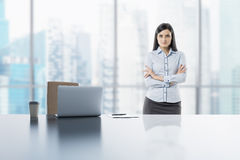 A young brunette lady with crossed hands in the modern panoramic office in Singapore. A laptop, notepad and a coffee cup are on th Royalty Free Stock Image