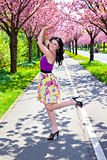 Young brunette lady dancing in a spring park stock images
