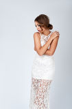 Young brunette lady in long white dress posing on grey backgroun Stock Photography