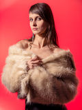 Young brunette lady in white fur coat Stock Photos