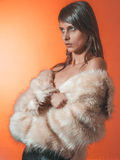 Young brunette lady in white fur coat Stock Image