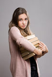 Young brunette with large pile of books. Stock Image