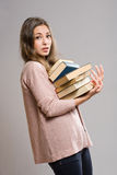 Young brunette with large pile of books. Stock Photo