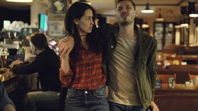 Young brunette is leading her drunk husband out of bar. Unshaven handsome young man is talking to his upset wife trying. Young pretty brunette is leading her stock video footage