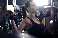 Young brunette lifting some weights and working on her biceps in Royalty Free Stock Photo