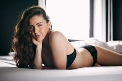 Young brunette in lingerie on bed Stock Image