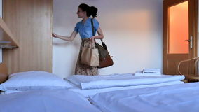 Young Brunette in Long Dress with Paper Bag is Coming Back at the Hotel Apartment After Shopping. Cute Woman Closes the stock video footage