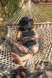 Young brunette lying resting sleeping in hammock with laptop in hand royalty free stock photography