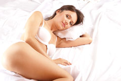 A young brunette is lying on a white silk bed Royalty Free Stock Photos