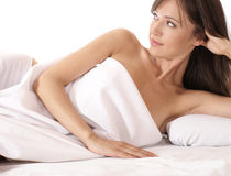 A young brunette is lying on a white silk bed Stock Photo