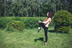 Young brunette makes athletic on the grass Royalty Free Stock Photo