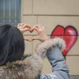 Young brunette making a heart with her fingers Stock Photo