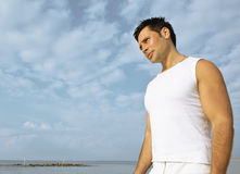 Young brunette man on beach at sea smiling Royalty Free Stock Photography