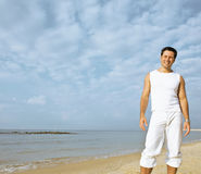 Young brunette man on beach at sea smiling Stock Image
