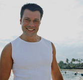 Young brunette man on beach at sea smiling Royalty Free Stock Images