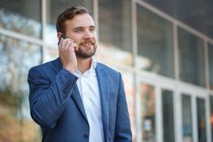 Young man speaks by mobile phone. Outside. Royalty Free Stock Image