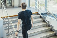 Young man climbing up the stairs at metro station. stock images