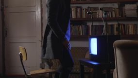 Young brunette man sitting on stool covers his face with hands and stands up. Young brunette man in grey jacket is sitting on small stool in front of turned on stock video