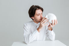 Young brunette man kissing fake skull Stock Photo