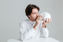 Young brunette man kissing fake skull and looking at camera Stock Photos