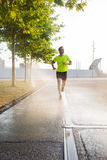 Young brunette man makes a morning jog outdoors while listening to music in headphones on his smartphone Stock Photos